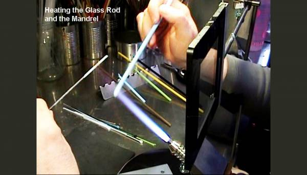 Heating the glass rod and continuing to keep the mandrel warm in the flame
