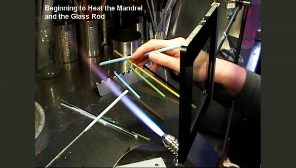 Beginning to heat the mandrel while keeping the glass rod warm in the flame